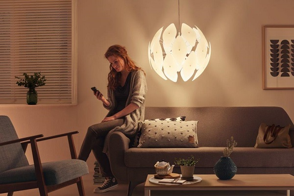 A Woman Checks Her Phone In Living Room Area Lit By Philips Smart Volume Pendants