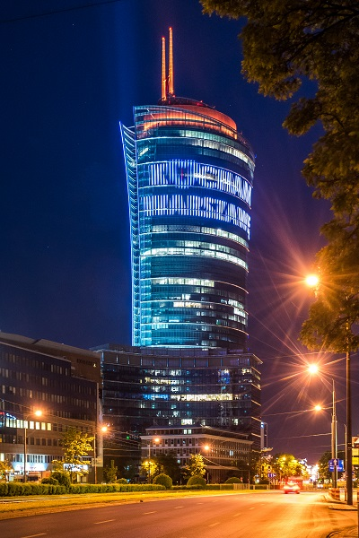 The building seen at night displays words and other advertisement slogans.