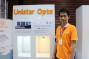 Darin Charang, Sales Representative, Unistar Opto poses in front of the company's LED bulbs. (LEDinside)